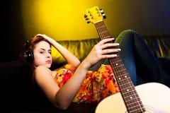 Mujer hermosa con los auriculares y la guitarra Fotografía de archivo