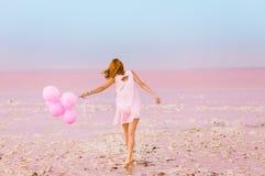 Mujer hermosa con los baloons en el lago de sal rosado fotos de archivo