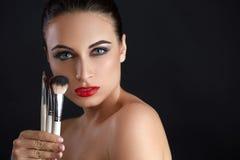 Mujer hermosa con los cepillos del maquillaje maquillaje Imágenes de archivo libres de regalías