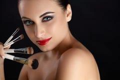 Mujer hermosa con los cepillos del maquillaje maquillaje Imagen de archivo