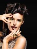 Mujer hermosa con los clavos de oro y el maquillaje de la moda Foto de archivo