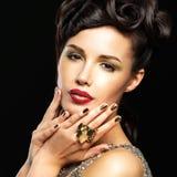 Mujer hermosa con los clavos de oro y el maquillaje de la moda Imagen de archivo