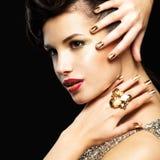 Mujer hermosa con los clavos de oro y el maquillaje del estilo Foto de archivo libre de regalías