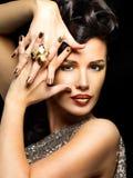 Mujer hermosa con los clavos de oro y el maquillaje del estilo Foto de archivo
