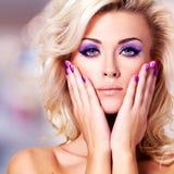 Mujer hermosa con los clavos púrpuras y el maquillaje del encanto Fotografía de archivo libre de regalías