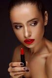 Mujer hermosa con los labios y el lápiz labial rojos brillantes a disposición Imagen de archivo libre de regalías