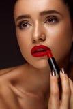 Mujer hermosa con los labios y el lápiz labial rojos brillantes a disposición Fotografía de archivo libre de regalías