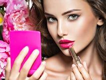 Mujer hermosa con los labios y la flor rojos brillantes cerca de la cara Imágenes de archivo libres de regalías