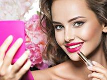 Mujer hermosa con los labios y la flor rojos brillantes cerca de la cara Foto de archivo