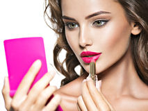 Mujer hermosa con los labios y la flor rojos brillantes cerca de la cara Imagen de archivo