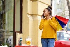 Mujer hermosa con los panieres usando el teléfono móvil Fotos de archivo libres de regalías