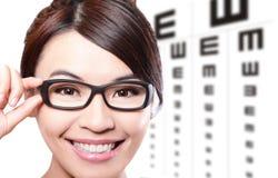 Mujer con los vidrios y la carta de prueba del ojo Imagenes de archivo
