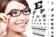 Mujer con los vidrios y la carta de prueba del ojo Imagen de archivo libre de regalías