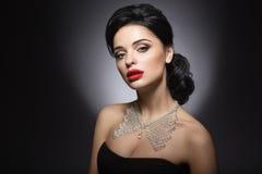 Mujer hermosa con maquillaje de la tarde, los labios rojos y el peinado de la tarde Cara de la belleza Foto de archivo