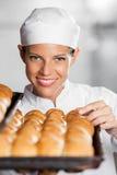 Mujer hermosa con panes recientemente cocidos Imagen de archivo