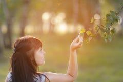 Mujer hermosa con respecto a las ramas de los árboles Fotografía de archivo