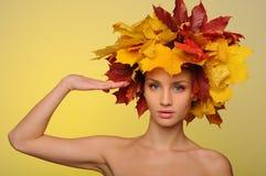 Mujer hermosa con saludar de las hojas de otoño Foto de archivo libre de regalías