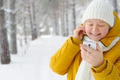 Mujer hermosa con smartphone a disposición, sonriendo, escuchando MU Fotos de archivo
