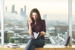 Mujer hermosa con smartphone y el libro Fotos de archivo libres de regalías