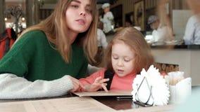 Mujer hermosa con su hija que mira el menú en un café de la pizzería almacen de video