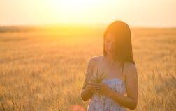 Mujer hermosa con un bouguet del trigo en campo de trigo en la puesta del sol Imágenes de archivo libres de regalías