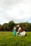 Mujer hermosa con un caballo en el campo Muchacha encendido Fotos de archivo libres de regalías