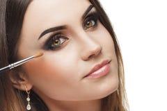 Mujer hermosa con un cepillo para el maquillaje cerca de la cara Foto de archivo