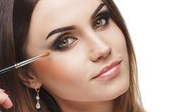 Mujer hermosa con un cepillo para el maquillaje en la mano Foto de archivo libre de regalías