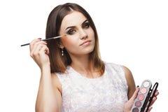 Mujer hermosa con un cepillo para el maquillaje y la paleta de sombreadores de ojos en las manos Fotos de archivo