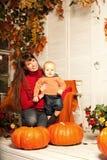 Mujer hermosa con un niño en el pórche de entrada con au de las calabazas Imagen de archivo libre de regalías