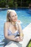 Mujer hermosa con con un pelo rubio largo, una figura delgada en un traje de baño del bikini sobre la piscina con agua azul brill Fotografía de archivo libre de regalías