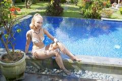 Mujer hermosa con con un pelo rubio largo, una figura delgada en un traje de baño del bikini sobre la piscina con agua azul brill Imágenes de archivo libres de regalías