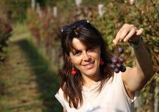 Mujer hermosa con un pequeño manojo de uvas en otoño Imagenes de archivo