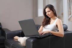 Mujer hermosa con una computadora portátil en un sofá en casa Fotos de archivo libres de regalías