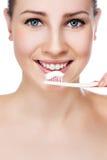 Mujer hermosa con una gran sonrisa que celebra el cepillo de dientes Fotos de archivo