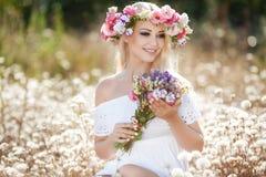 Mujer hermosa con una guirnalda de flores en campo del verano Foto de archivo libre de regalías