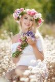 Mujer hermosa con una guirnalda de flores en campo del verano Imagen de archivo
