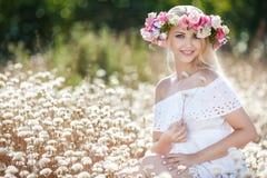 Mujer hermosa con una guirnalda de flores en campo del verano Foto de archivo