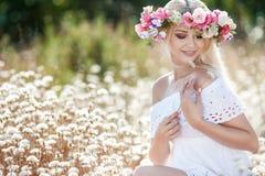 Mujer hermosa con una guirnalda de flores en campo del verano Imágenes de archivo libres de regalías