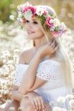 Mujer hermosa con una guirnalda de flores en campo del verano Imagen de archivo libre de regalías