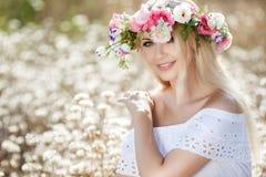 Mujer hermosa con una guirnalda de flores en campo del verano Fotos de archivo libres de regalías