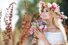 Mujer hermosa con una guirnalda de flores en campo del verano Fotografía de archivo