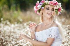 Mujer hermosa con una guirnalda de flores en campo del verano Fotos de archivo