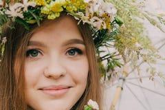 Mujer hermosa con una guirnalda en su cabeza de las flores reales fotografía de archivo libre de regalías