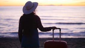 Mujer hermosa con una maleta en la playa soleada almacen de metraje de vídeo