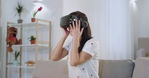 Mujer hermosa con una sonrisa hermosa blanca usando los vidrios de una realidad virtual de la nueva tecnología a explorar el vir