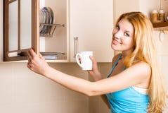 Mujer hermosa con una taza en la cocina Fotografía de archivo
