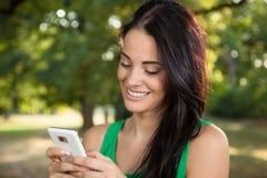 Mujer hermosa con usar el teléfono móvil Foto de archivo libre de regalías