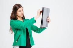 Mujer hermosa concentrada en la chaqueta verde que celebra el tablero y el dibujo Fotos de archivo