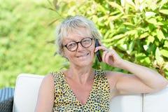 Mujer hermosa de 50 años con un teléfono móvil Fotografía de archivo libre de regalías